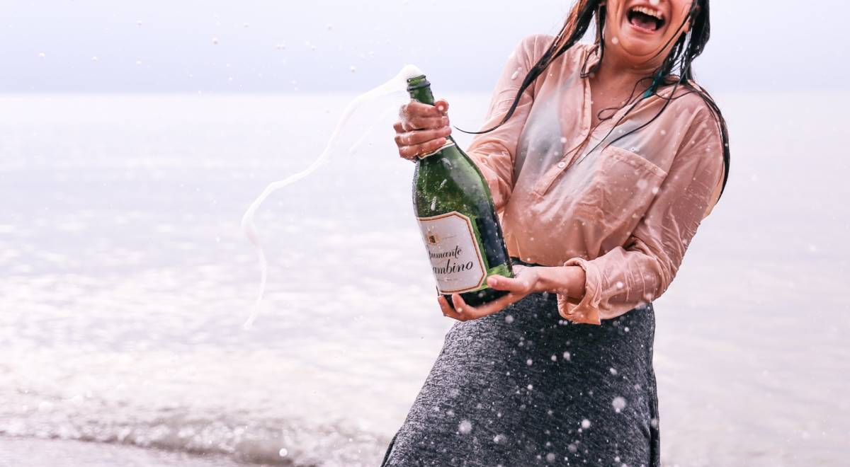 excited woman popping champagne